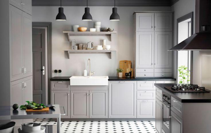 Et køkken i en landlig stil med grå fyldningslåger, sorte bordplader og forkromede knopper og greb
