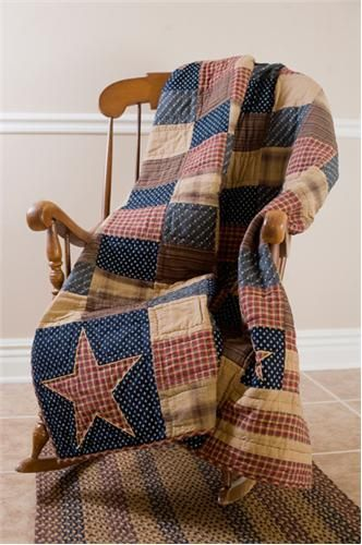 Americana patchwork quilt and pillows. looks a little worn and traditional. plus simple.
