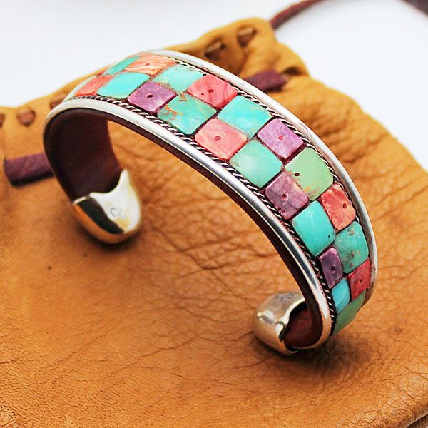 """Artist:  Charlie Favour- Anglo        Material:  Leather - Sterling Silver        Size:  1/2"""" x 5.5""""        Wrist:  7.0"""" or less        Origin:  Made In USA        Ships:  Within 1-2 business days      Charlie Favour Mosaic Leather and Silver bracelet featuring turquoise & two colors of spondylis shell mosaic.   Each bracelet has an opening of 1"""" to 1 1/2"""" and adjustments can be made by carefully bending the bracelet. Just add 1-1.5"""" to the length given to determine if it will fit your..."""