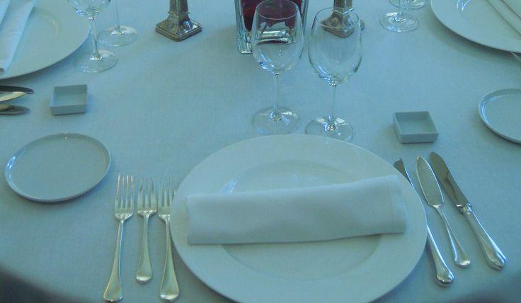 Una vez que hayamos preparado la mesa con sus manteles, cubremanteles, y su centro decorativo, como explicamos en el anterior post, el siguiente paso es colocar la vajilla, la cubertería, y cristalería para completar el montaje de la mesa. Para lograr tener una referencia y cierto orden, lo primero es colocar las sillas alrededor de …