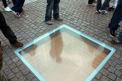 "book burning memorial, via Flickr. In the center of Bebelplatz, a glass window showing rows and rows of empty bookshelves. The memorial commemorates the night in 1933 when 20,000 ""anti-German"" books were burned here under the instigation of Goebbels. There's a plaque nearby that says something like ""Where they burn books, they will also burn humans in the end."""