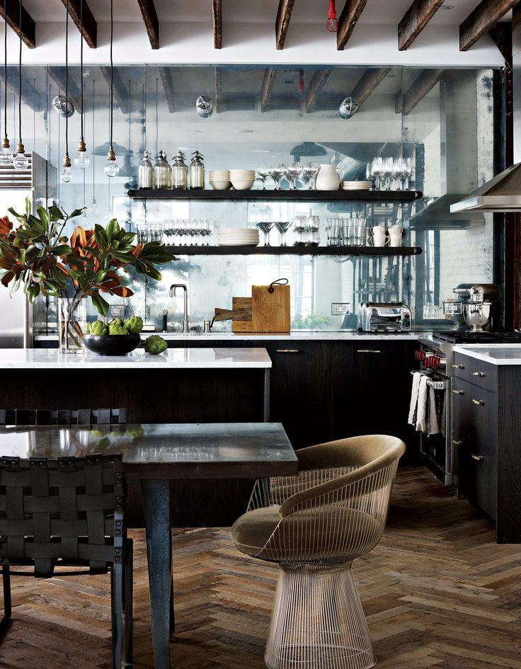An antiqued-mirror backsplash brings light into the kitchen.  The Platner armchair is by Knoll. The dining table is from Olde Good Things.  Photo: Francesco Lagnese