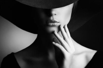 split lighting portrait. unique angle of the hat creates a mysterious mood in the model. black and white increases contrast.