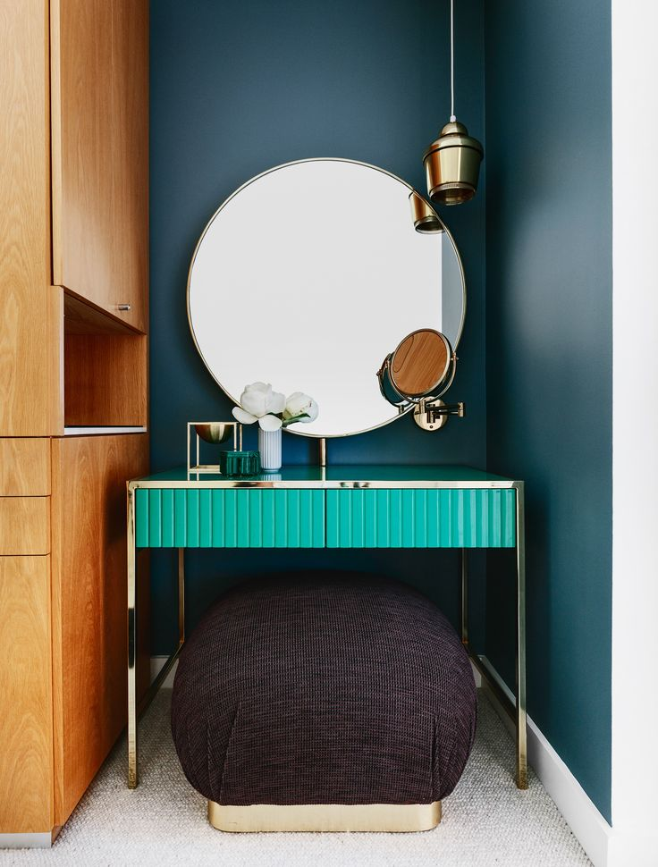 A luxurious emerald green dressing table with brass detailing is paired with round brass mirror and feature pendant in this Sydney Harbour apartment. Photography: Felix Forest   Styling: Steve Cordony   Story: Belle