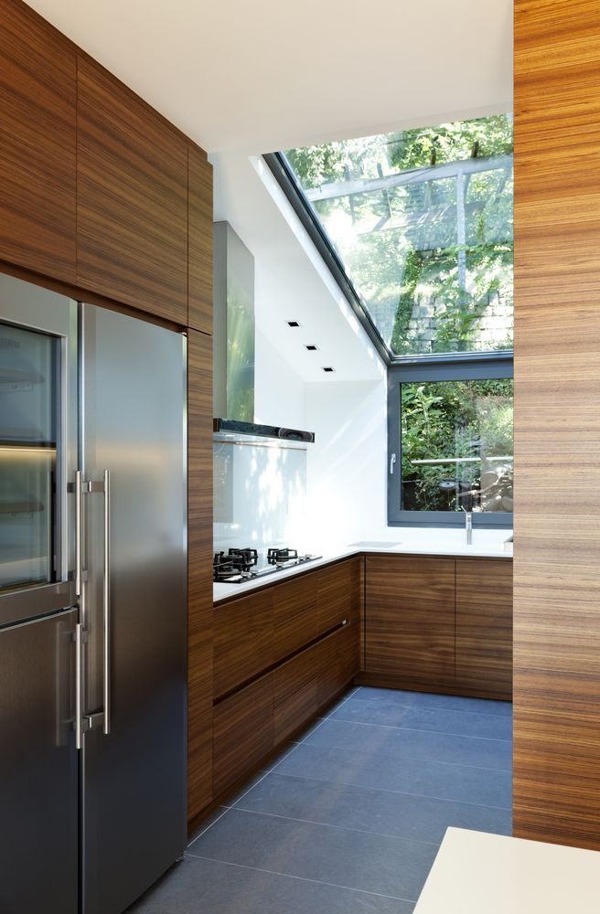Tiny natural wood kitchen with large window and skylight.  Sloped ceiling is partially glass.  Counter tops in white on top of natural wood cabinets.