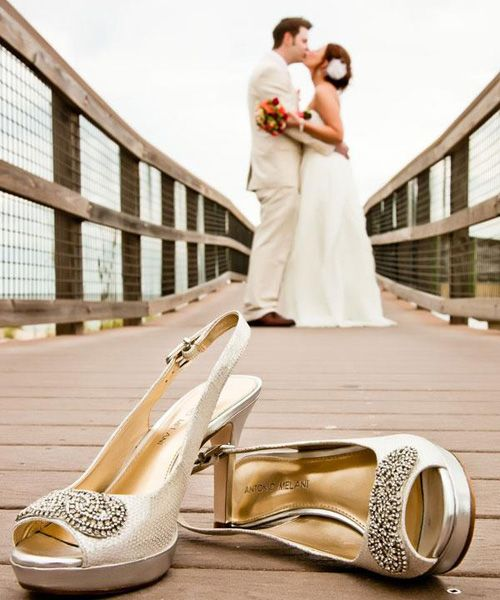 """Kick off your shoes for this memorable shot!    Why You Love It: """"Very cute!""""—Something Borrowed Bride  """"I have seen a los of photos high lighting the wedding dress alone. I like the concept of this photo better, the shoes, beach, and the kiss. Very well done!"""" —Cyhallatlanta    Photo Credit: Clear Skies Photography"""