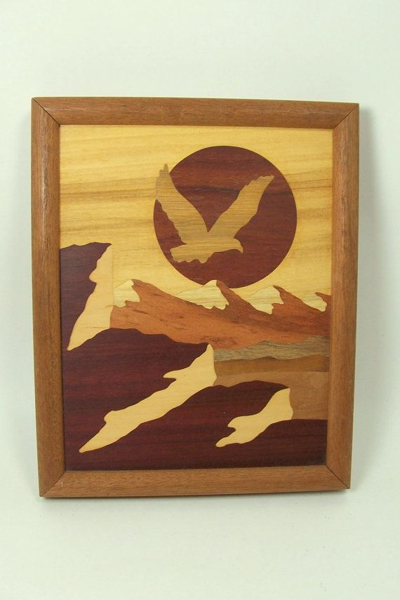 From the 1980s, a beautiful framed picture made of inlaid wood depicting and eagle flying across the sun with a mountainous background. This