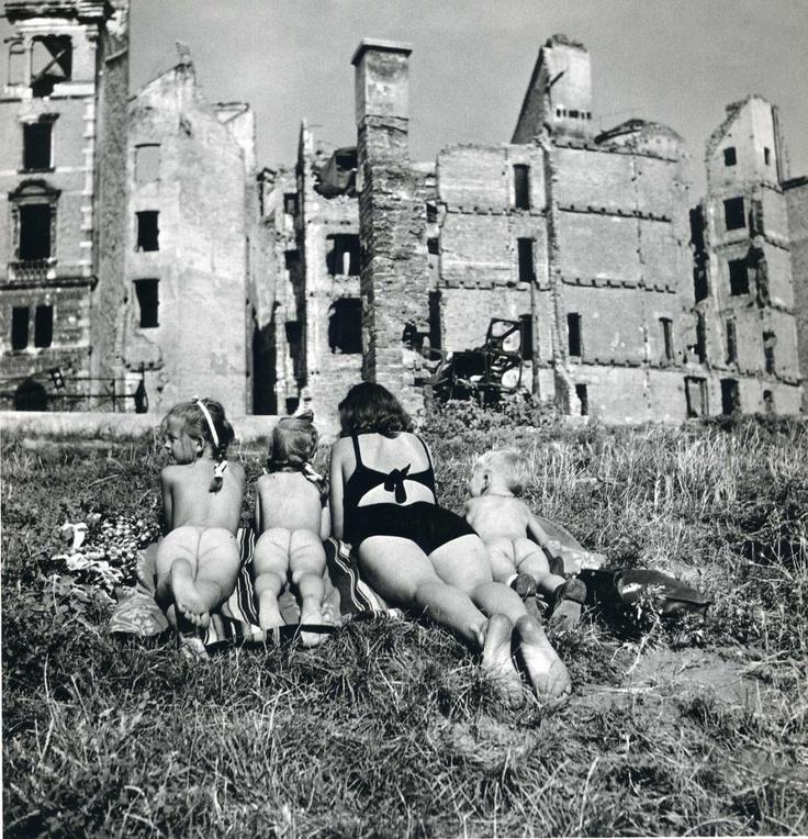 family sunbathing amongst the bombed buildings, Ernst Haas
