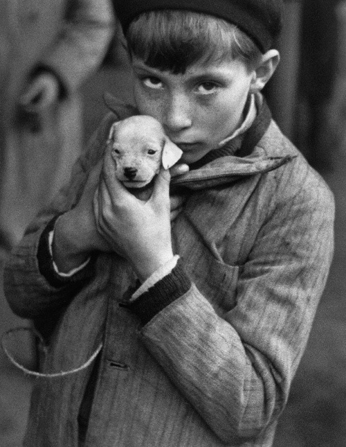A young boy protectively shows off his very tiny puppy. --- (Photo by Andre Kertesz)