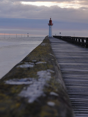 Lighthouse at the entry of the Deauville / Trouville-sur-Mer harbour in Basse Normandie, France with an evening sky