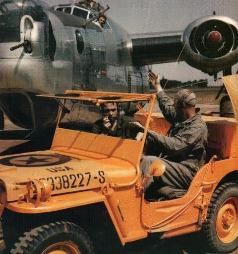 Brightly painted Willys MB Jeep leading B-24J aircraft at an unknown USAAF Air Field; note the special orange paint within National Insignia on hood, which changed colors when exposed to nerve agents