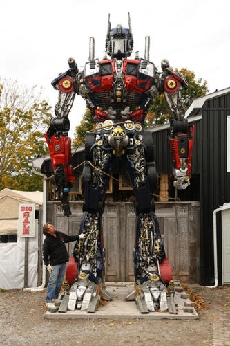 "FTA: ""Ron Dacey was looking for a 'wow factor' when he commissioned the seven-metre transformer robot that stands outside his antiques and crafts store on Highway 28 in Port Hope, Ontario, Canada."" Sweet! How about a junk Megatron so the two can battle it out?"