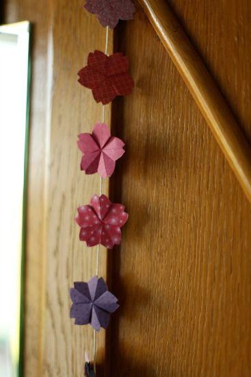 Envie de faire entrer le printemps chez vous? En quelques minutes réalisez cette élégante guirlande de fleurs en origami et décorez joliment votre intérieur!
