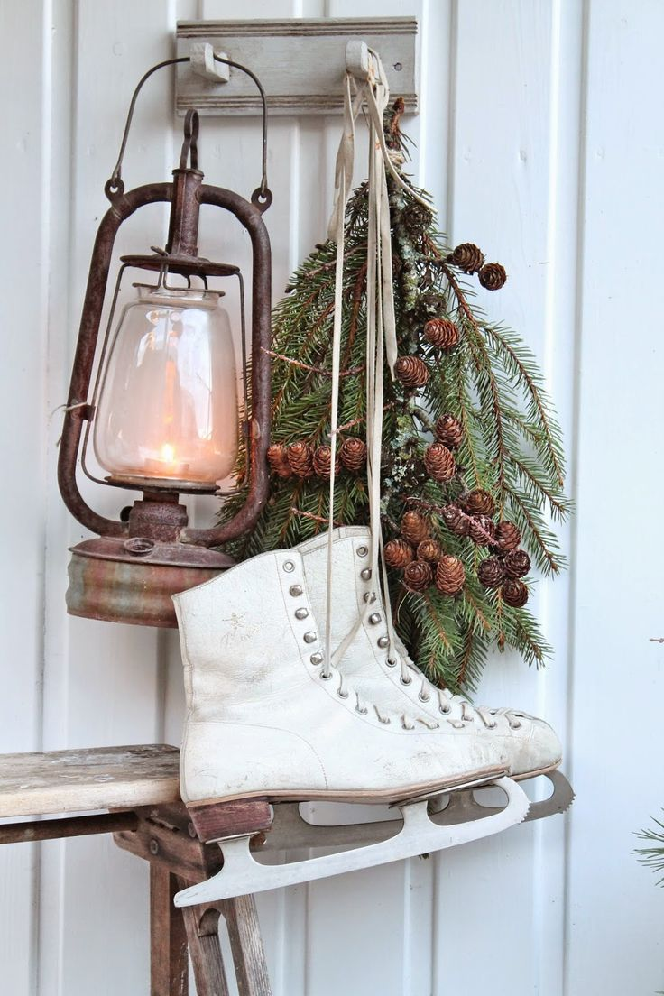 Nordic winter- vintage rusty lantern, old white ice skates, evergreen boughs with berries hanging on country planked wall