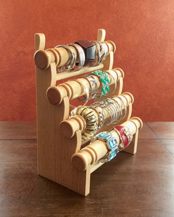 A beautiful way to display your finely made bracelets! Made from real wood, this 4 tier bracelet display can hold multiple bracelets securely with 4 easy removable bars to conveniently remove and replace bracelets. Easy to pack and transport to trade shows, craft shows, festivals and exhibits.  No screws, no metals used, just excellent craftsmanship you can see from the quality of work - the result of which is a stunning bracelet display. Showcase your gorgeous bracelet pieces in this…
