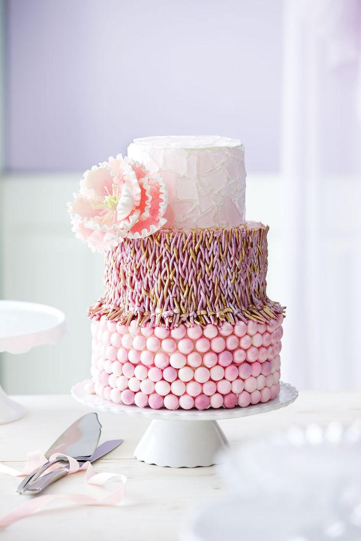 Rock candy, braided licorice and pink mints look incredible together as accents to decorate this exquisite three-tiered wedding cake.