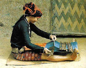 Tejedora con telar de cintura en la provincia de Hainan. Jili Nacionalidad. Esta joven está haciendo un brocado elaborados, como por ejemplo en la falda, usando un sencillo telar de cintura. Al inclinarse hacia delante o hacia atrás, ella controla la tensión de la urdimbre.