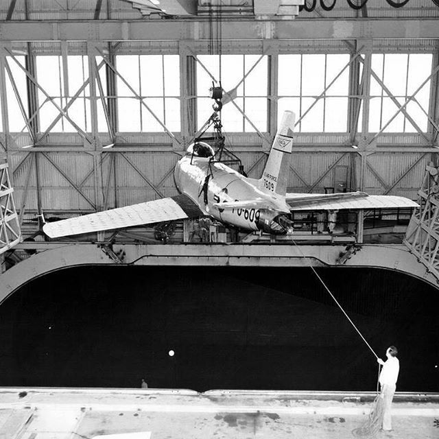 explorenasa #TBT An F-86 aircraft is lowered into the 40 x 80 Foot Full Scale Wind Tunnel at the NACA Ames Aeronautical Laboratory, Moffett Field California. Behind the aircraft and out of view, a crane operator lowers the jet as a mechanic holds a guide rope aligning the F-86 with supporting struts located down in the tunnel. Once the jet is mounted on the struts, tunnel doors visible on either side of the aircraft's wings will close to form an air tight seal. #throwback #retro #ames #nasa…