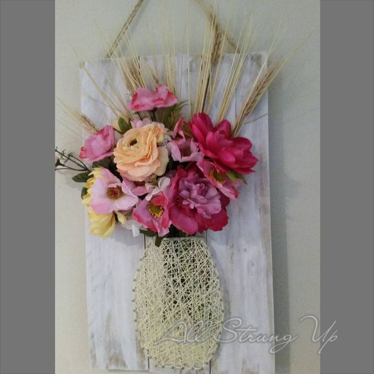 hanging flower vase string art on a white wash board