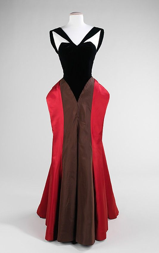 Black, brown, and red silk and wool evening dress (front) by Charles James, American, 1946. The construction of this dress reconfigures the body by having the harder draped fabric brought forward and soft fabric at the back, the opposite from the norm, giving the appearance of front and back being reversed. The startling color contrast and different reflective qualities of satin, wool-backed crepe and faille in the skirt reinforce this deception. The form of the hips bears witness to James'…