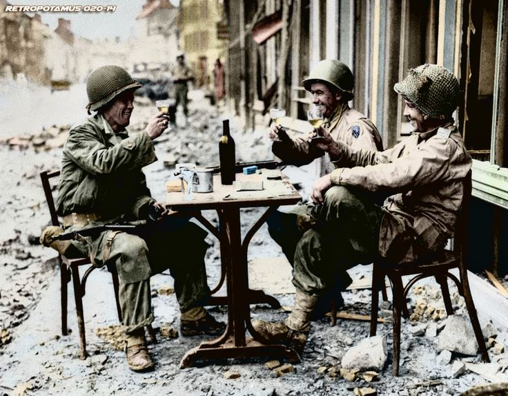 An American version of a sidewalk cafe, in fallen La Haye du Puits, France on July 15, 1944, as Robert McCurty, left, from Newark, New Jersey, Sgt. Harold Smith, of Brush Creek, Tennessee, and Sgt. Richard Bennett, from Wilkes Barre, Pennsylvania, raise their glasses in a toast.