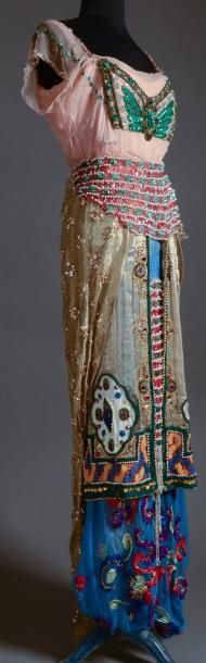 """Evening ensemble, by Jeanne Paquin in collaboration with Léon Bakst, summer 1912, Hôtel Drouot. Bakst, a Russian painter, helped engineer the success of the Ballets Russes, for which he produced numerous costumes and sets. In 1912, he was commissioned by Jeanne Paquin to develop some of his Daphnis and Chloë costume designs into a series of """"fantasies of modern dress"""" fashion designs."""
