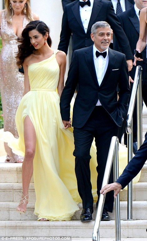 Here they come: The beautiful barrister looked sensational in a simple pale yellow gown as...