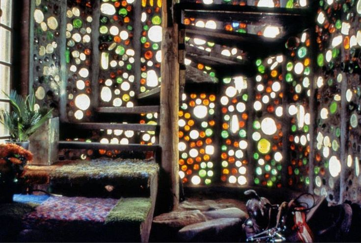 Glass bottles catching the sunlight cast many hues in this beautiful Earthship interior.