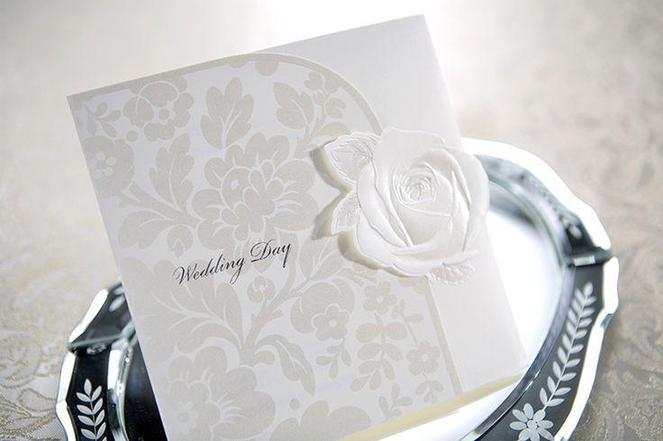 """B0017 är ett inbjudningskort med ett svagt mönster av skimrande champagneblommor. Inbjudningskortet är även dekorerat med en utskuren ros, som också håller det stängt. På framsidan återfinns den silverfolierade texten """"Wedding Day"""". Se alla våra bröllopskort på www.exklusivia.se"""