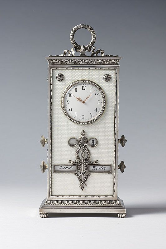 A large Imperial guilloché enamelled desk clock and calendar by Fabergé, of rectangular upright form, enamelled translucent opalescent oyster white over a guillochage, centred to the top by a circular pearl set bezel, with a flaming silver torch entwined by laurels, surmounted by a laurel wreath tied with a bow. Workmaster: Johann Victor Aarne, St. Petersburg, pre 1896. Purchased by the Dowager Tsarina Maria Feodorvona from Fabergé's St. Petersburg shop on 9th March 1898 for 600 roubles.
