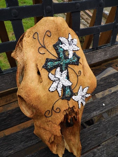 Measures 17 1/2 long, 8 1/2 wide and 6 in depth. Cow skull is stained with a copper toned stain and embellished with stabilized turquoise chips,