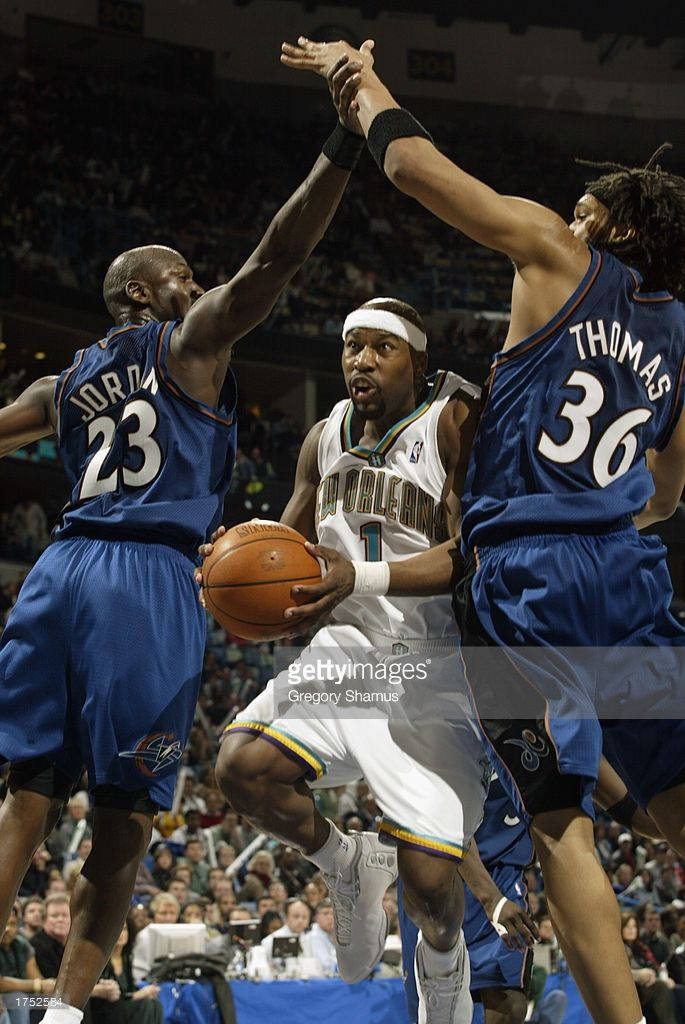 Baron Davis #1 of the New Orleans Hornets splits the defense of Michael Jordan #23 and Etan Thomas #26 of the Washington Wizards during the game at New Orleans Arena on January 22, 2003 in New Orleans, Louisiana. The Hornets won 103-94.