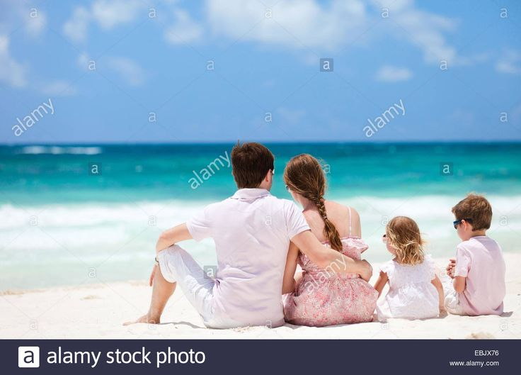 family with two children admiring the view on Caribbean beach, Mexico Stock Photo