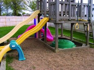 Pea sized gravel for playground floor.  Also like the addition of small plastic store bought playset next to the wooden one.