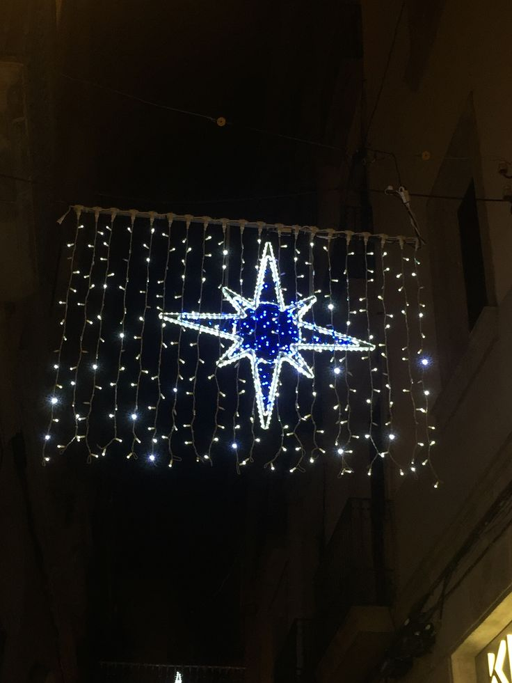 This decoration is located on Carrer de Montsio next to Placa Catalunya. It depicts a compass symbolizing a star and contains a very deep blue light with an outline of white lights as well as tiny sparkling LEDs as well.