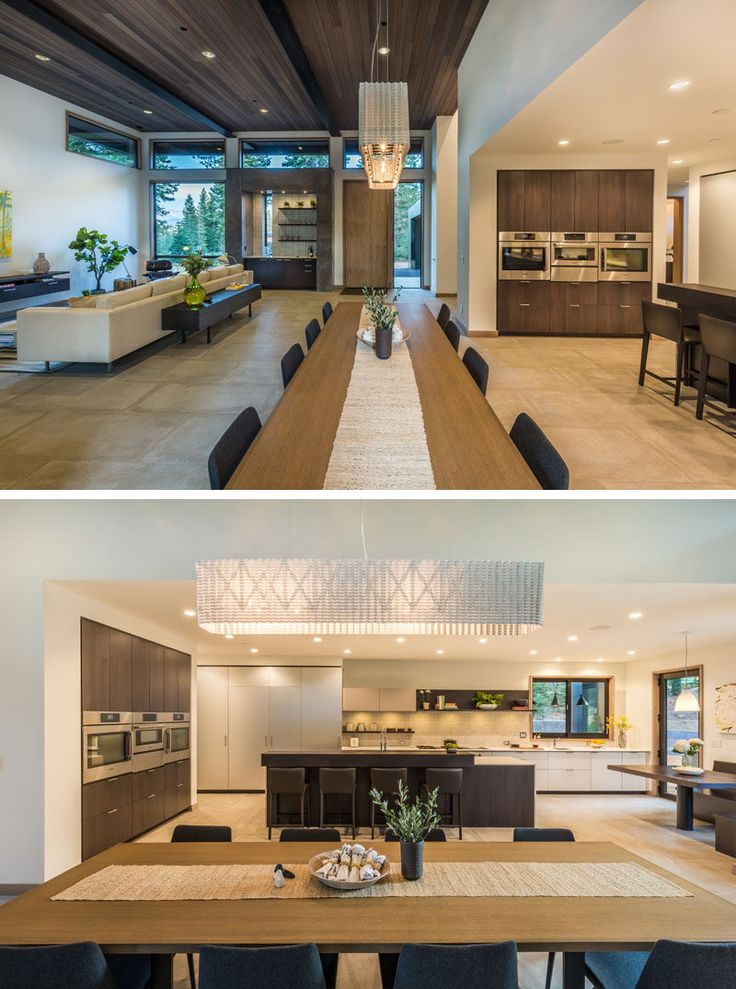 In this modern home, a long dining table separates the living room from the kitchen, and a large pendant lamp anchors the dining area within the open floor plan.