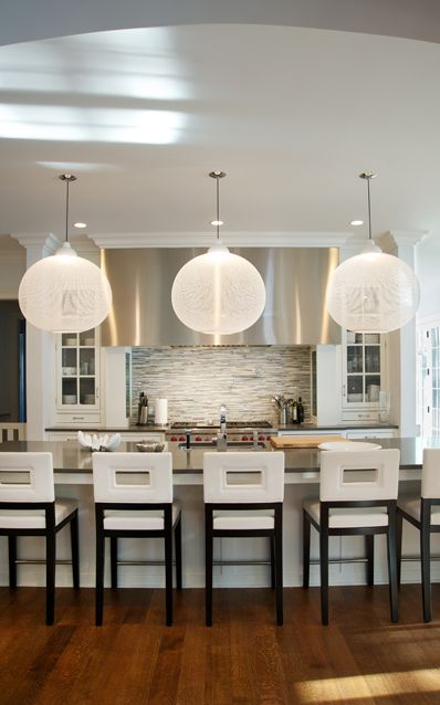 Spacious modern kitchen with oversized orb pendant fixtures. Crisp, Contemporary White Leather Barstools from Overstock.com. Spice colored hardwood floors, stainless steel range hood and appliances.