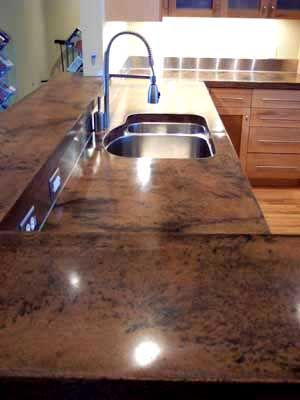 Beautiful finished concrete kitchen countertops with a custom burnished copper color featuring black marbling.