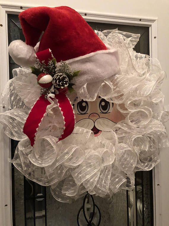 This jolly Santa Claus Wreath will welcome everyone with a smile. The center Santa face is painted on a 12 inch metal disc. I then added white snowball mesh to complete his hair and beard. A Santa hat and holly complete this wreath. It measures 24 inches and is ready for immediate