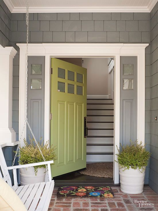 A classic Craftsman color palette gets a modern pop of color with an avocado-green door and potted plants. The family considers the covered porch an extra room in the house./