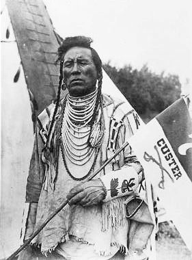 Older Curly (Ashishishe) (c1856-1923). Crow Indian (Montana). Active Crow warrior against Sioux enemies. Scout for the U.S. Army. Survivor in the Battle of Little Big Horn June 1876. First to report U.S. defeat. Highly sought after media figure. Married 2 times. 1 daughter. Farmer-breeder. Crow Police. Died of pneumonia in 1923. (Wikipedia) - Photographer not known - c1912.