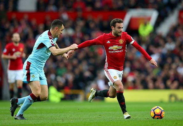 Juan Mata of Manchester United and Dean Marney of Burnley compete for the ball during the Premier League match between Manchester United and Burnley...