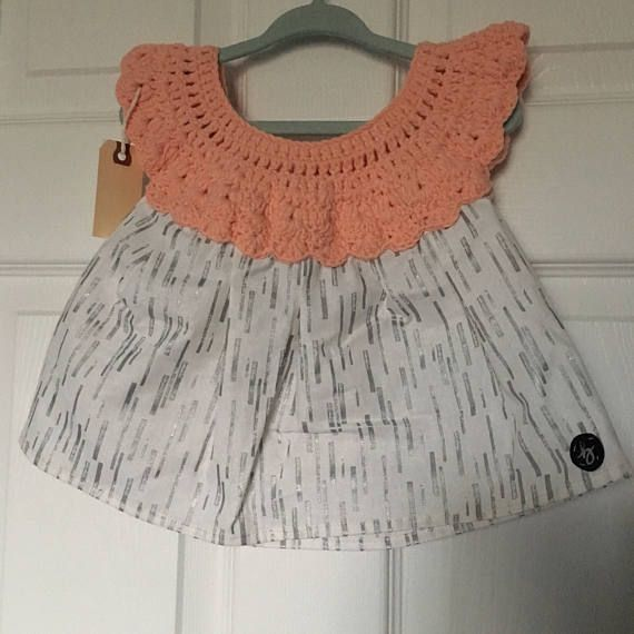 12-18 month size handmade baby girl dress with crochet top in peach cotton/nylon/polyester blend yarn with white & silver pattern cotton fabric skirt, fastened at the back with a button. Lightweight and pulls over the head.