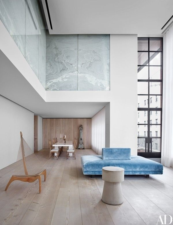 The living/dining area features a Jørgen Høvelskov chair (left), a borne, dressed in a blue Scalamandré velvet, by Jill Dienst and Stephen Sills, and circa-1750 Swedish chairs around a Piero Lissoni table   archdigest.com