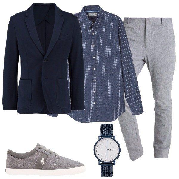 Una camicia a pois bianchi su fondo blu, abbinata a giacca in cotone, blu, a due bottoni, con tasche laterali. Propongo, inoltre, pantaloni grigi in lino e cotone, sneakers basse, grigie, in pelle e tessuto e orologio in acciaio inossidabile.
