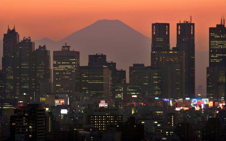 O pico mais alto do Japão, Monte Fuji, ergue-se sobre os arranha-céus do distrito de Shinjuku, em Tóquio