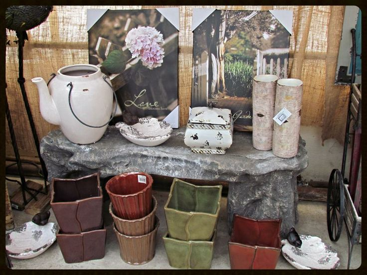 White watering can, spring prints, small pots, cedar candle holders, birdbaths.