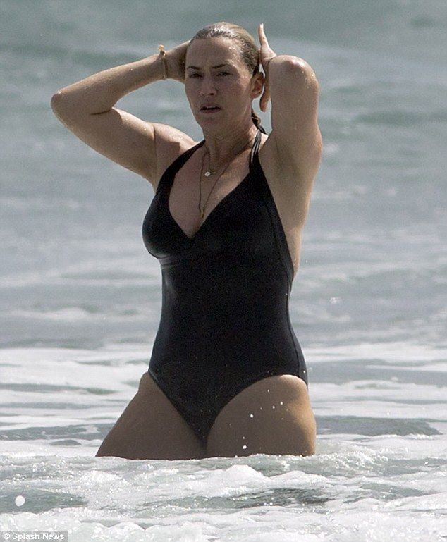 Making waves: Kate Winslet stepped out in a plunging black swimsuit as she took a dip in t...