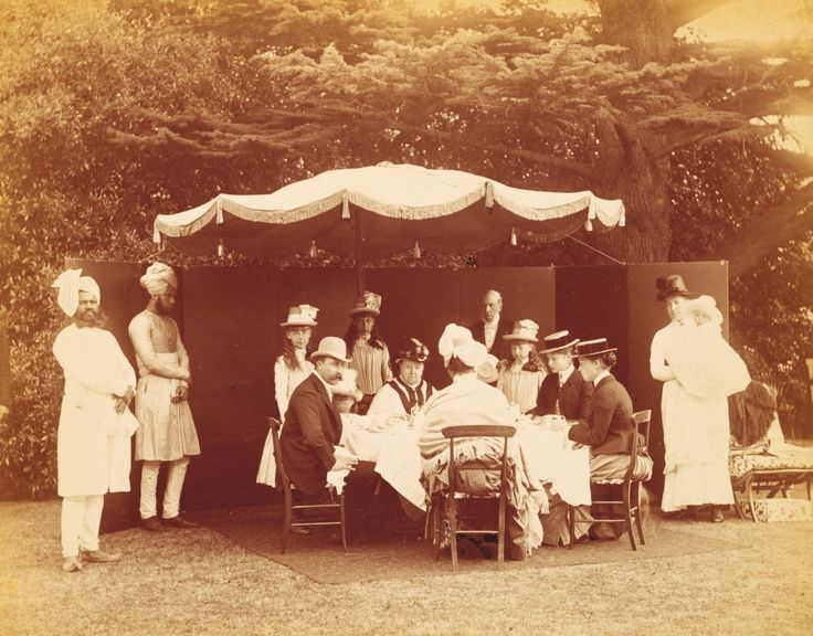 Queen Victoria and her family having breakfast around an outdoor table at Osborne House, including Princesses Marie and Victoria Melita of Edinburgh, The Duke of Connaught; Princess Beatrice; Princess Alix of Hesse; Princess Alexandra and Princess Beatrice of Edinburgh; Princess Irene of Hesse, also includes servants Abdul Karim, Stephen Maslin and Muhammed Bukhsh all standing behind the party and there is a nurse holding Prince Alexander of Battenberg.