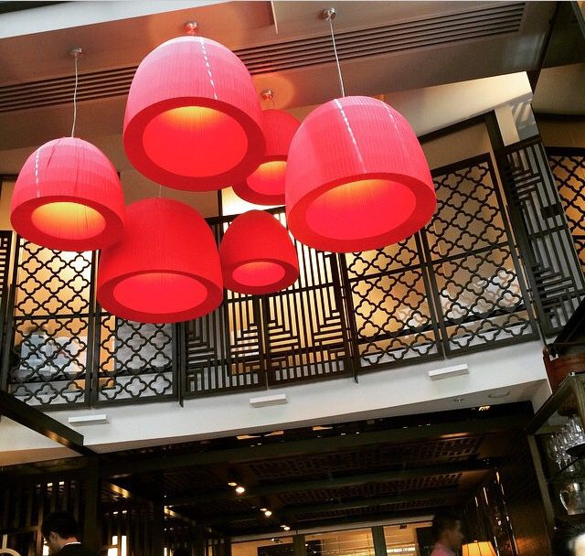 Lucky Chan restaurant Crown Casino The colour scheme is very dark throughout.  These red pendants are striking against the dark colours and the soft round shapes contrast against the hard geometric shapes of the panels.
